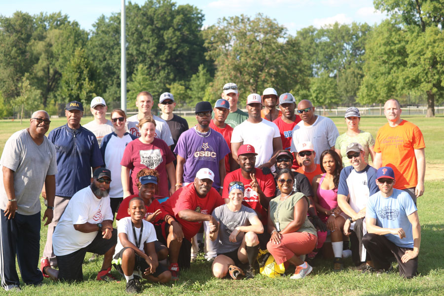 Organizers, players, family members, and both teams pose for a photo after an afternoon of baseball at the 10th annual Step Up to the Plate: Strike Out Violence softball game. /Kaitlyn Moore