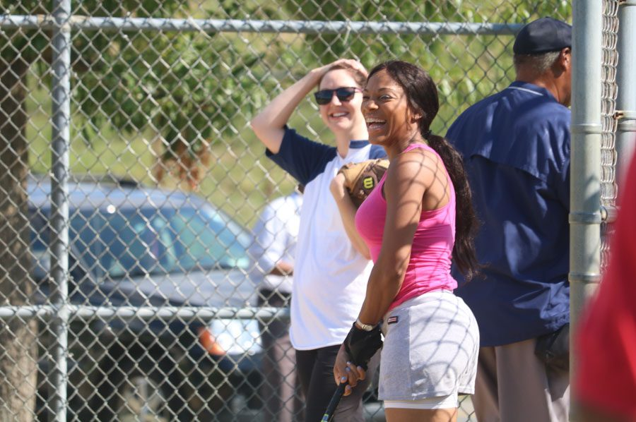 Strawberry Mansion teammate, Ebony Williams, right, shares a laugh with FBI catcher during the 10th annual Step Up to the Plate: Strike Out Violence softball game. /Kaitlyn Moore