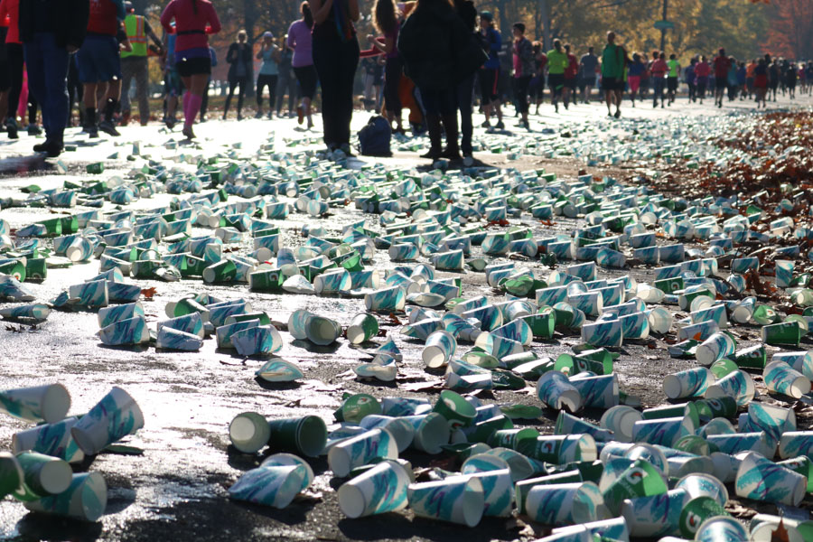 Hundreds of paper cups used from runners who already passed through the hydration station were raked by volunteers to the side of the course./Kaitlyn Moore