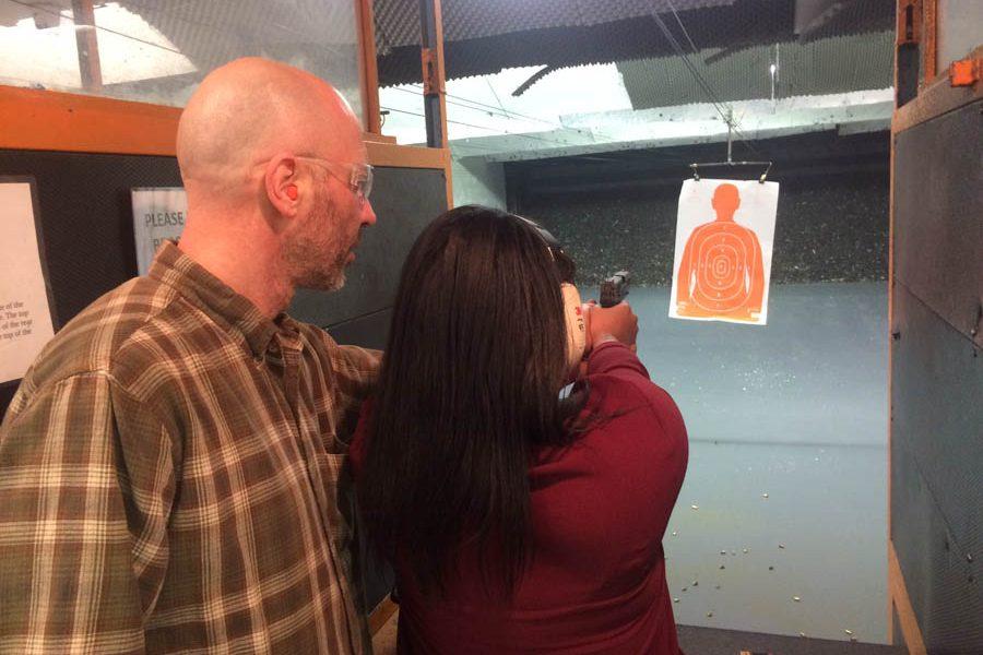 Yuri Zalzman instructs Jamila Lopez on how to use a handgun./Steve Bohnel