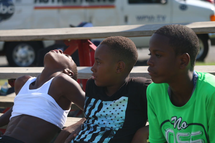 Jahmarr Gardner, right, and Naji Reid Lawrence Lewis look on during the softball game in support of their friend Alex, the pitcher on Strawberry Mansion's team./Kaitlyn Moore
