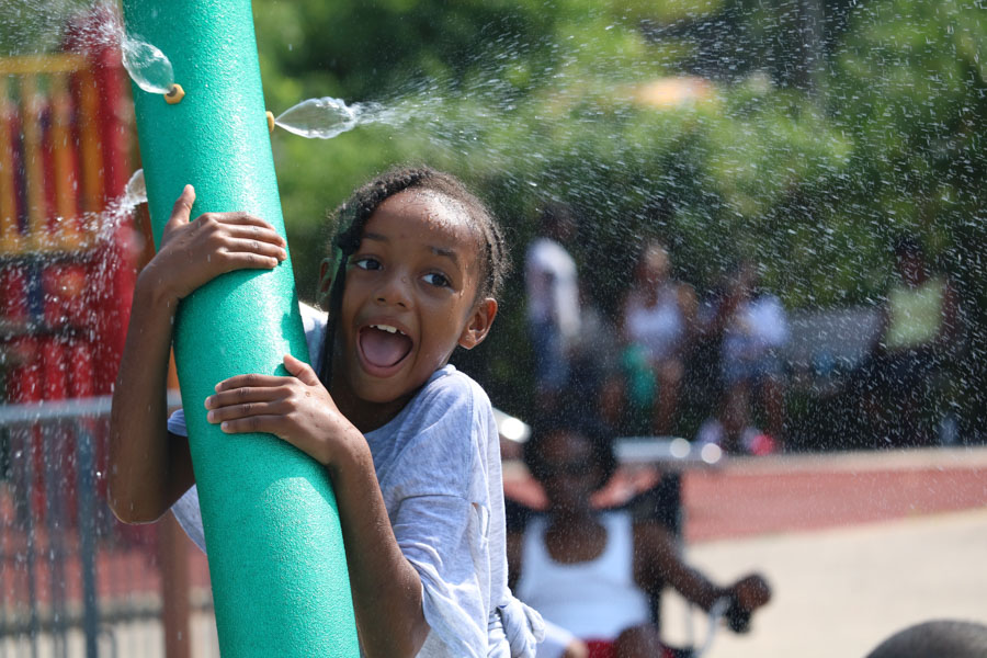 A young girl enjoys the water sprinklers at Mander Playground during Strawberry Mansion day.