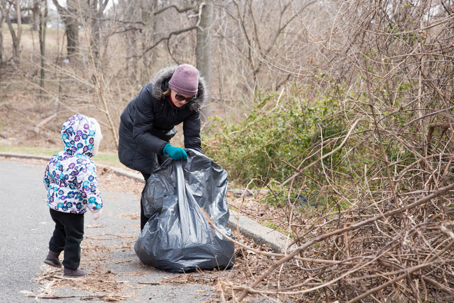 "Fairmount resident Abby McShea, who lives ""across the street"" from Lemon Hill Park with her husband and daughter, places a piece of found trash into a bag. Besides her stands her daughter, Paige, 2."