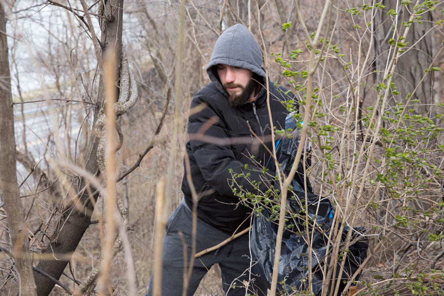 Shaun Cerborino, the brainchild behind the March 11 park cleanup, places trash into a bag.