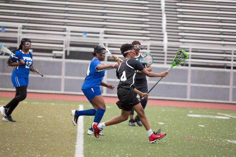 "Nadirah ""Slim"" McCray cuts through opposing defenders on her way to scoring a goal. /Patrick Clark"